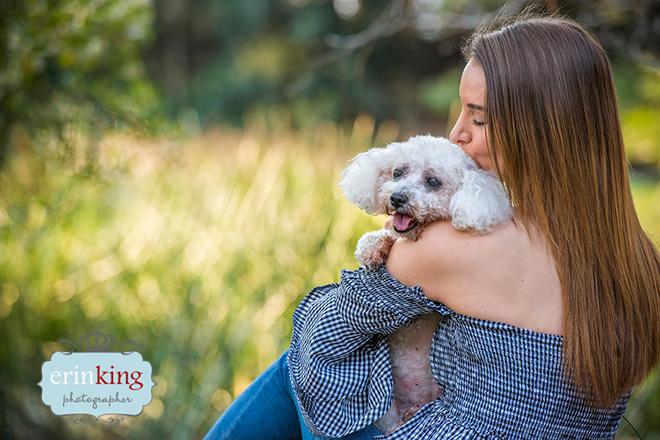 woman cuddling bichon dog