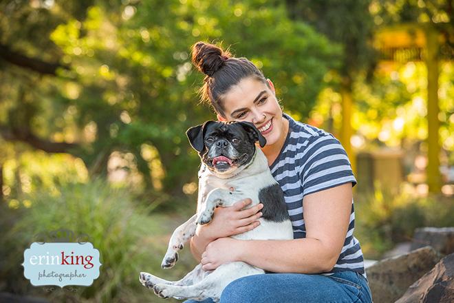 woman cuddling pugalier dog
